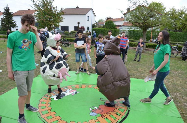 Deze kinderen wagen zich aan een spelletje 'koeworstelen'.