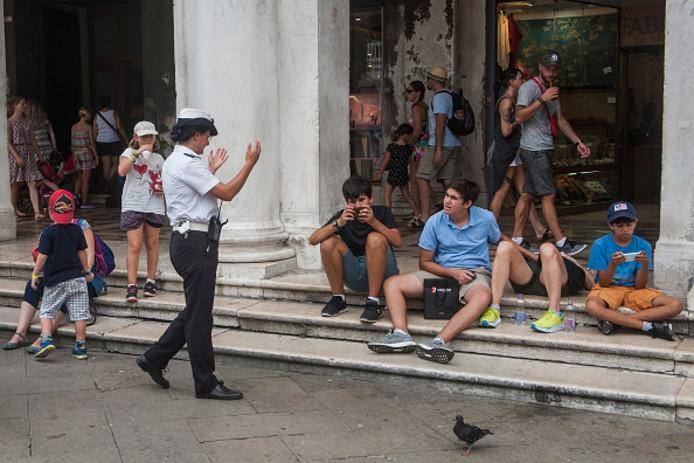 Een agente legt jonge toeristen uit dat het verboden is om te gaan zitten op de trappen rond het San Marcoplein. Foto Luca Zanon/Getty Images)