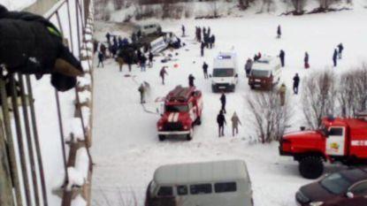 Toeristenbus stort vanop brug naar beneden op bevroren rivier in Siberië