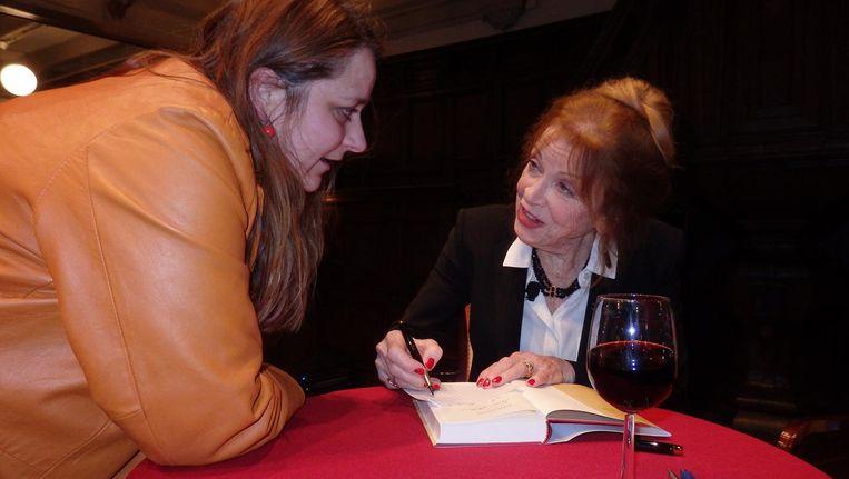 Sonja Barend (r) signeert haar autobiografie, hier voor Abys Kovacs-Wieg. 'Ik had dit niet kunnen schrijven toen mijn moeder nog leefde' Beeld Schuim