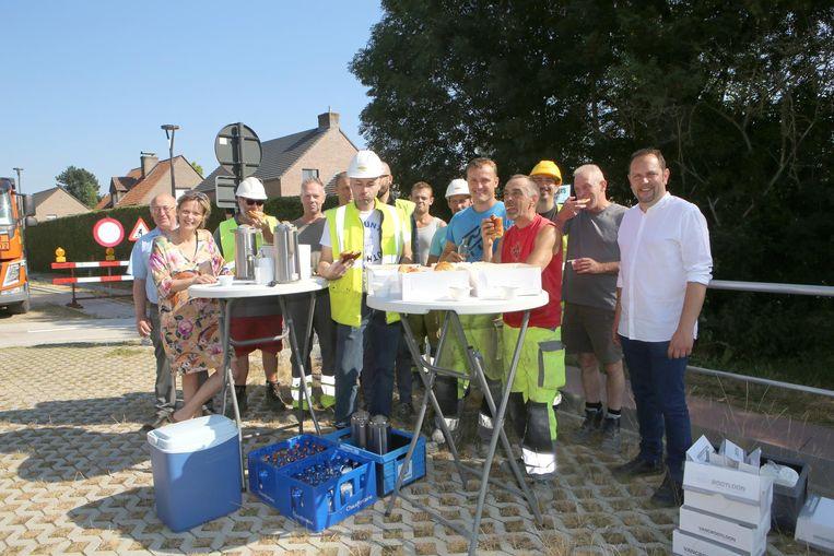 De stadsarbeiders genieten van een koffiekoek alvorens weer aan de slag te gaan.