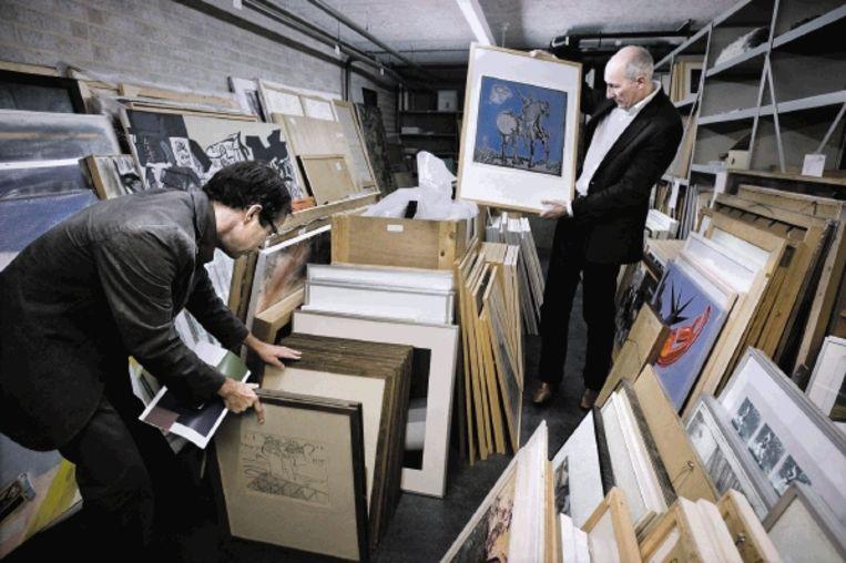 Wethouder Henk Beerten (rechts) grasduint door de gemeentelijke kunstcollectie die nu nog ruim 3000 stuks telt. (FOTO KOEN VERHEIJDEN) Beeld