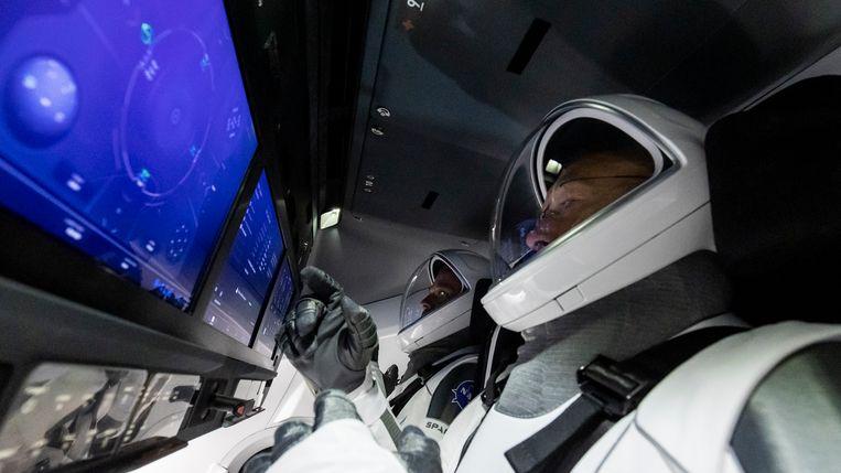 Astronauten Doug Hurley (vooraan) en Bob Behnken trainen aan boord van de Crew Dragon. Beeld SpaceX