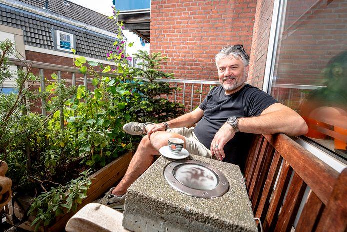 Stefan van der Laan Bouma op zijn balkon met het brandgrenslampje als tafeltje.