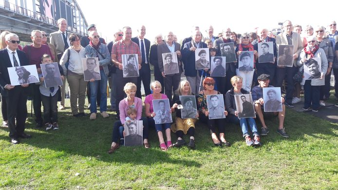 Nabestaanden van tijdens de Slag om Arnhem gesneuvelde militairen poseren voor de John Frostbrug. Ze tonen de portretten van de jongemannen van toen die niet meer naar huis terugkeerden.