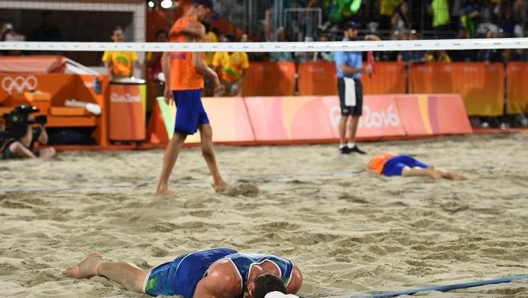 Alison Cerutti (L) viert de overwinning, op de achtergrond treuren Alexander Brouwer (R) en Robert Meeuwsen Beeld anp