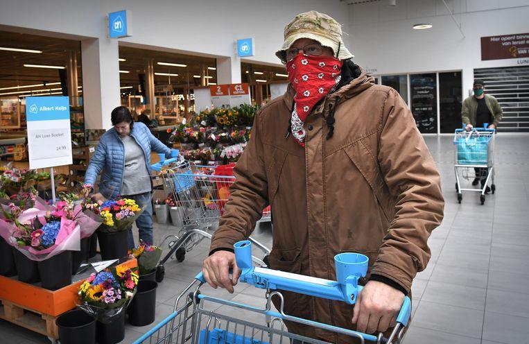 Sinds kort geldt een dringend advies om in openbare binnenruimten een mondkapje te dragen. Maar winkels, zoals deze Albert Heijn in Tilburg, hoeven het hun klanten niet te verplichten. Beeld Marcel van den Bergh / de Volkskrant