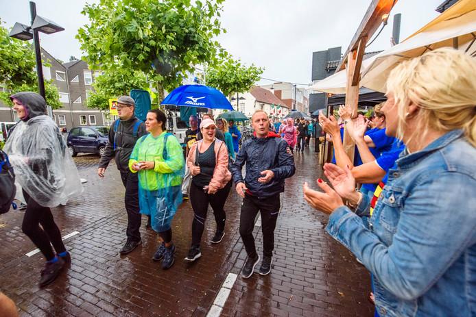 Lopers van de Kennedymars worden in Asten aangemoedigd door het publiek.