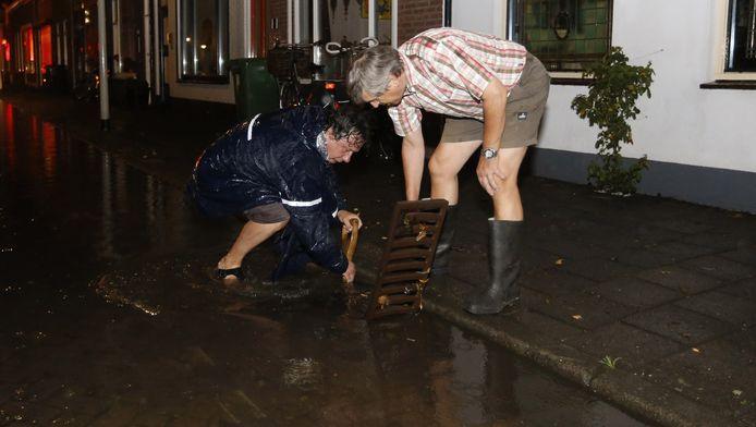 Bewoners proberen een put open te krijgen na noodweer in Bergen op Zoom vorige week.
