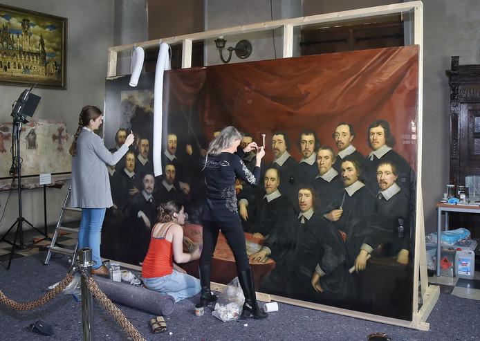 Morgane Noly (links), Johanne Jusselme (midden, zittend) en Marjan de Visser (rechts) werken aan de restauratie van het schilderij.