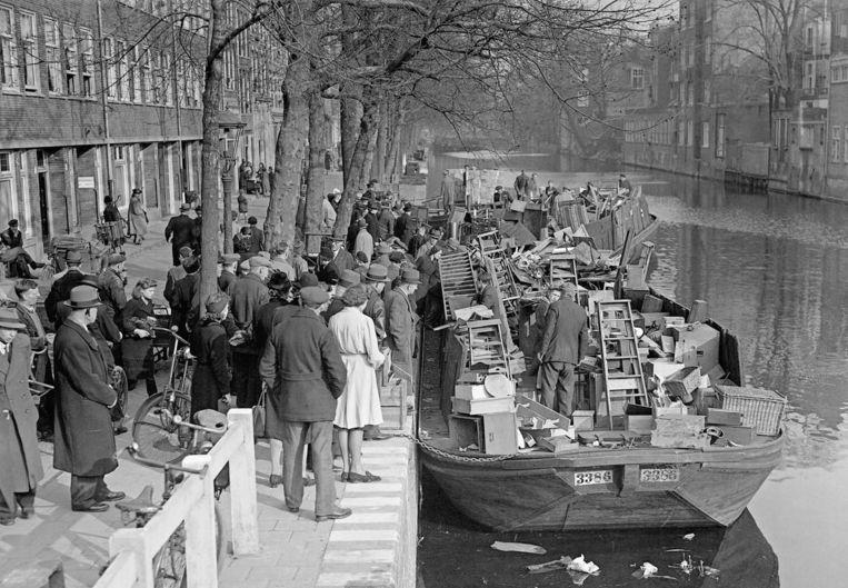 Op de Lijnbaansgracht werden in maart 1943 dekschuiten volgeladen met huisraad van gedeporteerde Joden. Ze moesten hun huissleutels afgeven waarna hun woning werd verzegeld en leeggehaald. Omstanders toonden grote belangstelling voor de spullen Beeld J.D. NOSKE/ANP/Spaarnestad