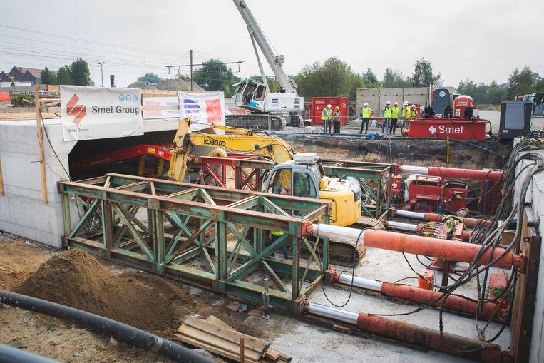 De betonnen fietstunnel wordt met hydrolische pompen door de treinberm geperst.