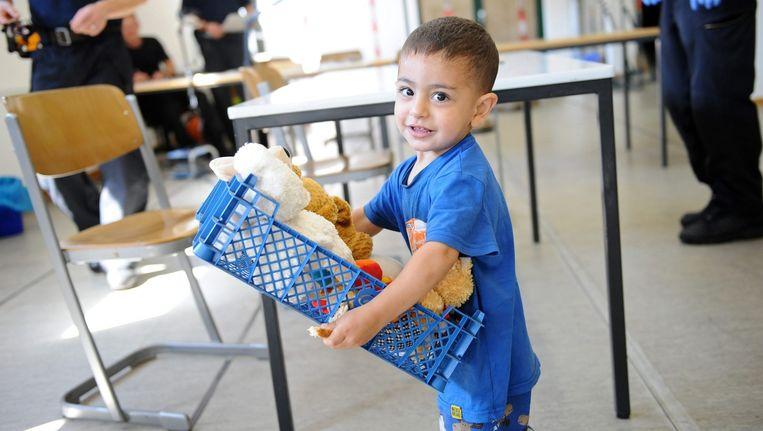 Een jongetje uit Syrië draagt een krat met knuffels in Rosenheim in Duitsland. Beeld EPA