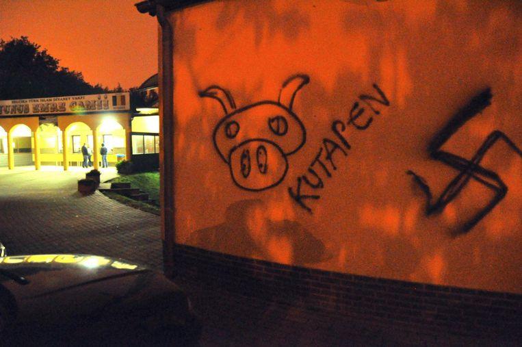 Een hakenkruis, een varkenskop en het woord 'kutapen' op een muur van de Turkse moskee in Sledderlo.