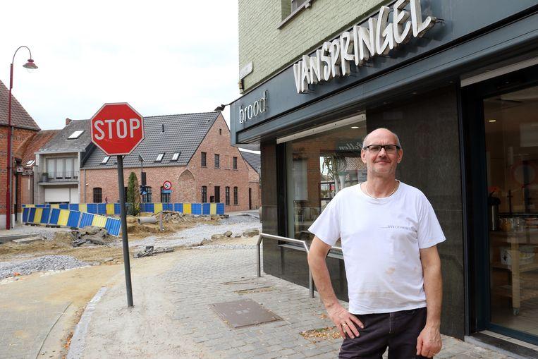 Ignace Vanspringel aan zijn bakkerij, met vlakbij de opengebroken weg.