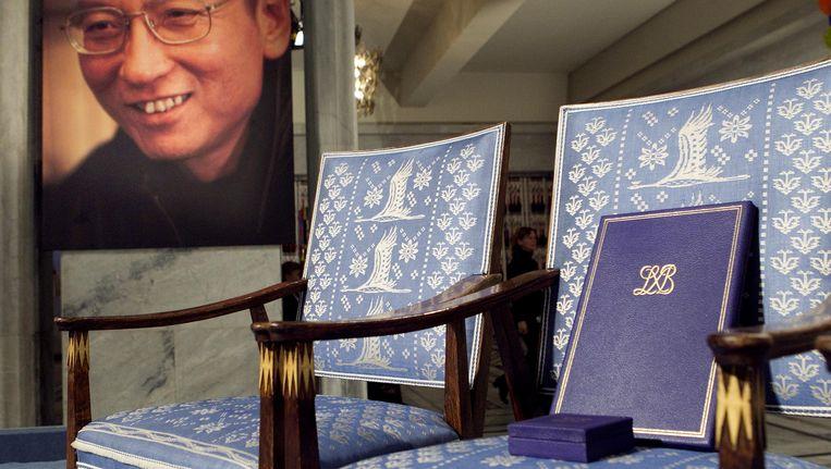De lege stoel symboliseert waar Liu Xiaobo (achtergrond) had moeten zitten tijdens de Nobelprijsuitreiking vorig jaar. Beeld AP