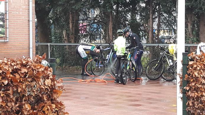 Deelnemers aan de Wintertocht spuiten na afloop hun mountainbike schoon.