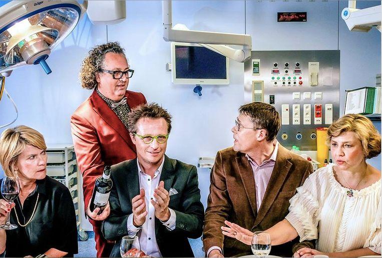 De vijf artsen spelen het diner, hier voor de gelegenheid met een dokterkabinet als decor