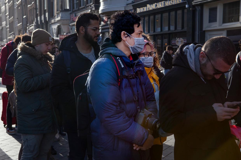In Amsterdam loopt een handje vol toeristen rond die een mondkapje dragen uit bescherming tegen het Coronavirus.