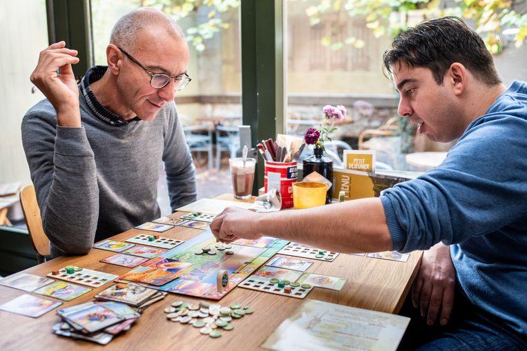 Bioloog Menno Schilthuizen (links) en wetenschapsredacteur George van Hal spelen het bordspel Evolution: Climate. Beeld Simon Lenskens