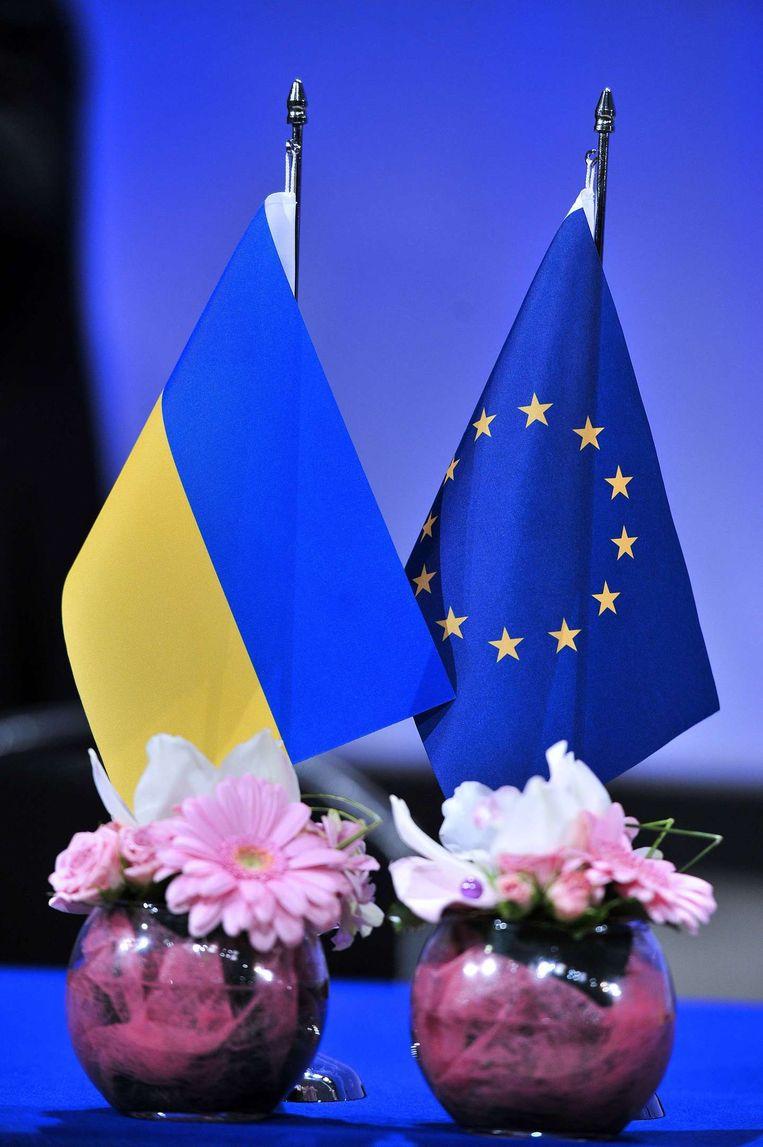 Een Oekraïense en Europese vlag bij de ondertekening van de overeenkomst Beeld afp