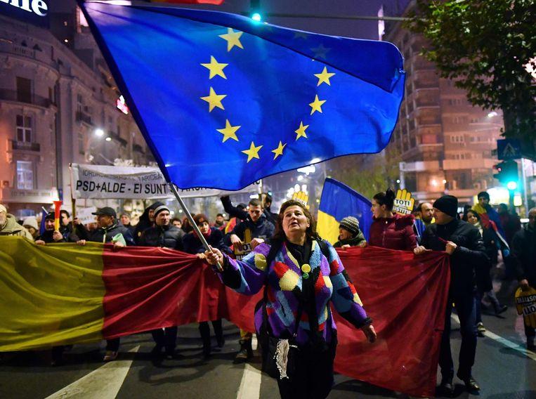Een vrouw zwaait met een Europese vlag tijdens een protest tegen de regering en corruptie in Boekarest, Roemenië. Beeld AFP