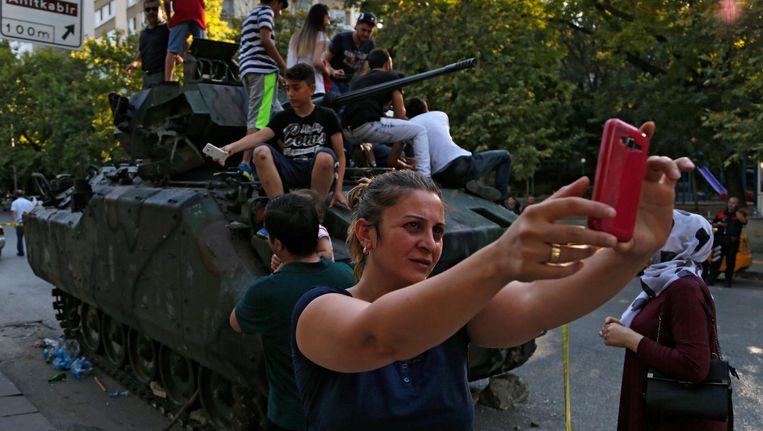 Een vrouw maakt een selfie bij een door betogers overmeesterde tank, afgelopen zaterdag in Ankara. Beeld ap