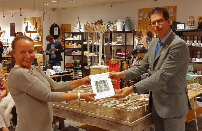 Erika Klein Kranenbarg (links) overhandigt het eerste exemplaar van haar fotoboek aan burgemeester Joost van Oostrum in Borculo.