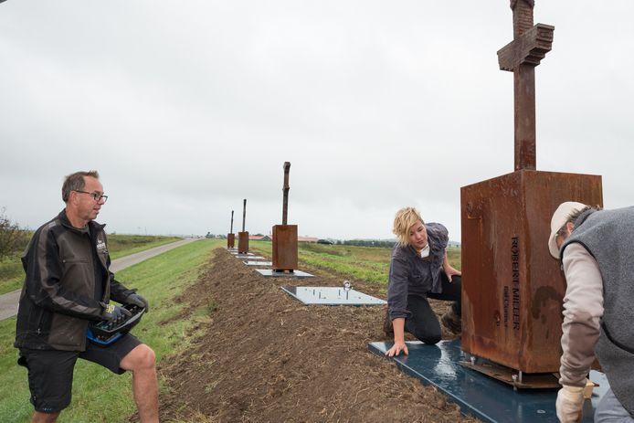 Rosalinde van Ingen Schenau zet met bevriend kunstenaar Marco de Jong (rechts) en Hans Stouten van bouwbedrijf Boogert (links) het door haar ontworpen monument op z'n plek. Ze maakte het in opdracht van de Stichting Cultuur en Erfgoed Brouwershaven (SCEB).