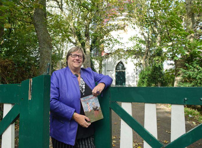Mineke Straijer bij de ingang van de vuurtoren in Haamstede waar ze als kind naast woonde. De als een zuurstok gestreepte Westerlichttoren staat in de steigers, maar ook de groene deur die toegang gaf tot de toren komt in het boek Vuurtorenkind voor