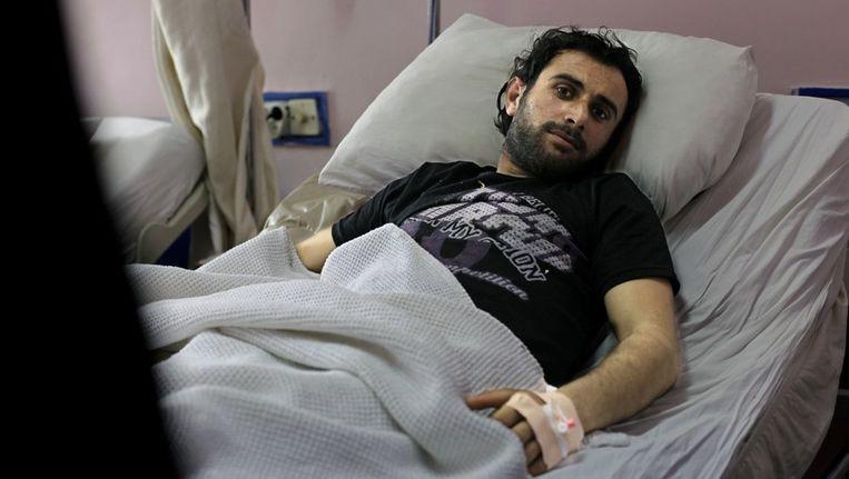 Khaled Asram, die tijdens zijn vlucht werd geraakt door een kogel, in een ziekenhuis in het Turkse Antakia. Beeld afp