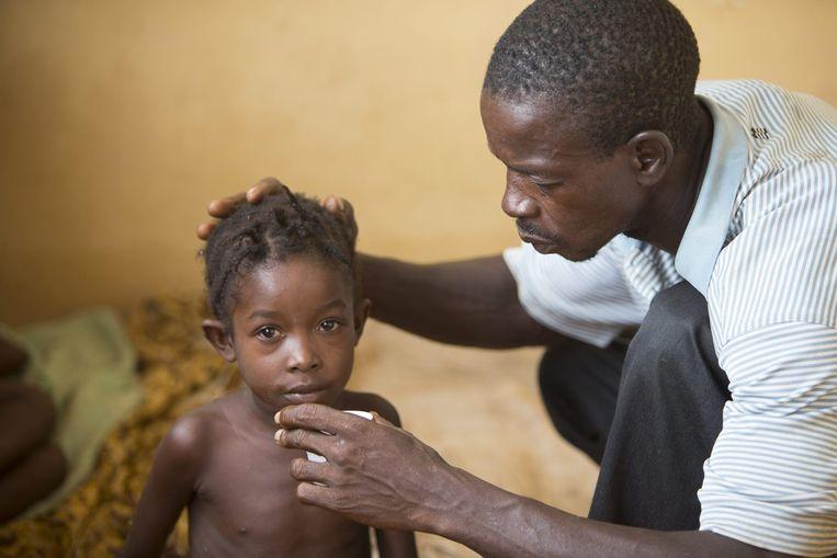 Een kind in Sierra Leone dat mogelijk ebola heeft wordt verzorgd door de vader. De moeder en enkele familieleden zijn eerder al overleden. De zeer besmettelijke dodelijke ziekte grijpt vooral om zich heen in Sierra Leone, Liberia en Guinee. Daar zijn al meer dan 4000 mensen overleden. In het Westen zijn enkele gevallen in de VS en Spanje. Beeld reuters