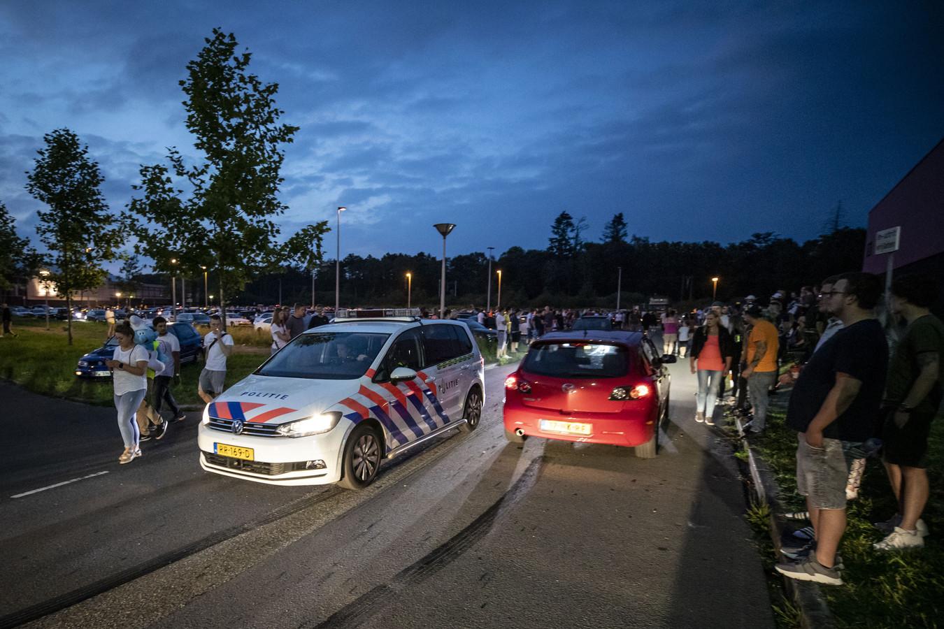 Rond 22.00 uur, als het hoogtepunt van de carmeeting nadert, rijdt een politiewagen een rondje over de parkeerplaats van IJsbaan Twente.