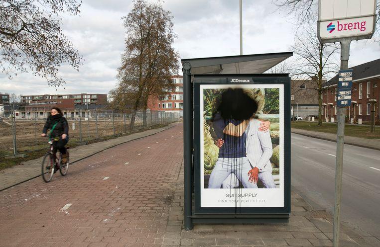 Een met zwarte verf bekladde campagneposter van Suitsupply met twee zoenende mannen bij een bushalte in de Arnhemse wijk Presikhaaf. Beeld Hollandse Hoogte / Luuk van der Lee Fotografie