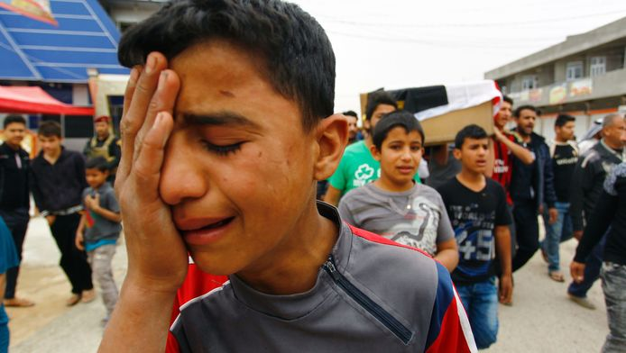 Familie en vrienden van tijdens de voetbalwedstrijd omgekomen slachtoffers rouwen bij hun begrafenis.