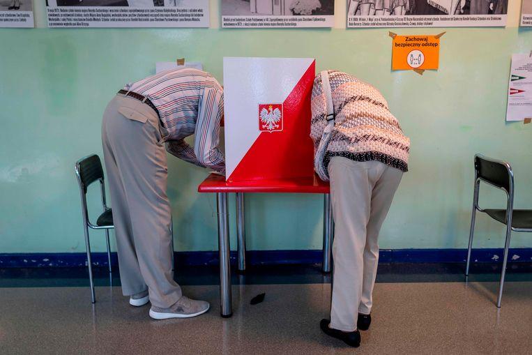 Twee mensen brengen hun stem uit in Warschau.  Beeld AFP