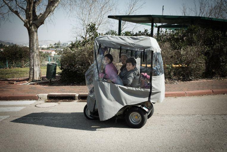 Kinderen rijden met hun oma door de nederzetting Kfar Tapuach op de Westelijke Jordaanoever.  Beeld Daniel Rosenthal