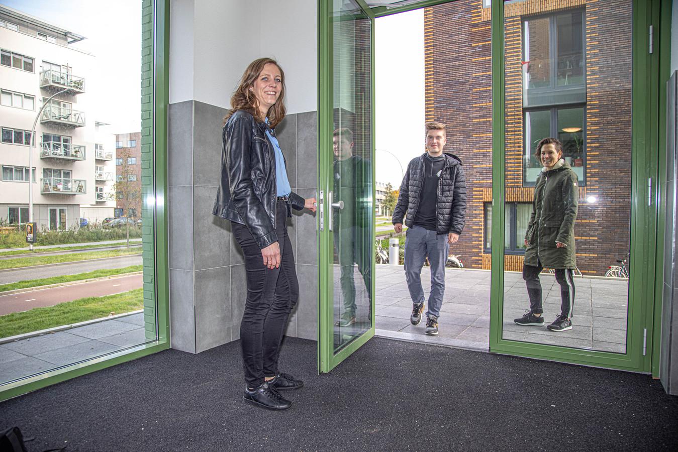 Jordi Schrotenboer is een van de bewoners van de nieuwe woonvorm in de vierde studentenflat. Eline Ploegman houdt de deur voor hem open, rechts Lareina van Enteren.