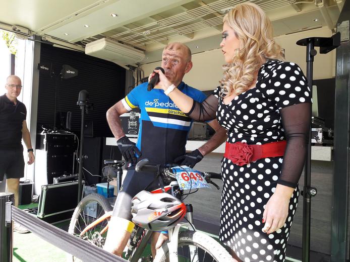 Patty Pitt interviewt Frans Willems, die als eerste van 540 deelnemers aan de Vrijthof-Vrijthof Bike-Challenge over de meet in Hilvarenbeek kwam