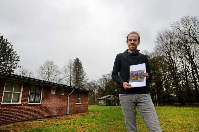 Bart Enserink voor de vroegere scoutinggebouwen van De Paalsteek. In zijn handen heeft hij een globaal bouwplan voor het ecohuis.