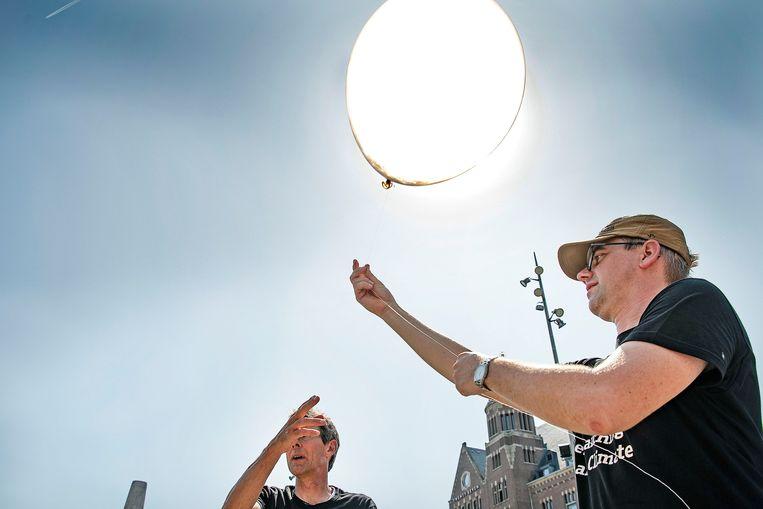 Het Amsterdam Institute for Advanced Metropolitan Solutions laat een weerballon op de dam om de hitte te meten. Beeld Guus Dubbelman / de Volkskrant