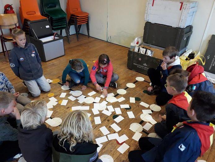 Kinderen van de scouting maken kerstkaarten voor de ouderen in Brouwershaven.