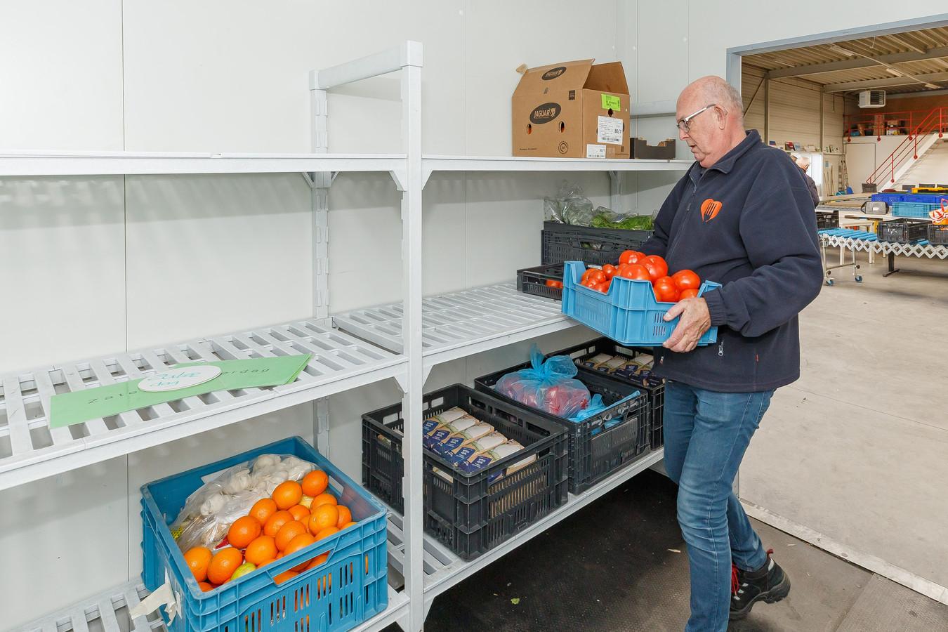 Een vrijwilliger van de voedselbank in Zwolle vult de schappen weer aan.