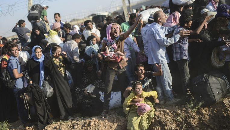 Syriërs vluchten zondag bij Akçadale naar Turkije via kapotte hekken en gaten in de grond. Beeld afp