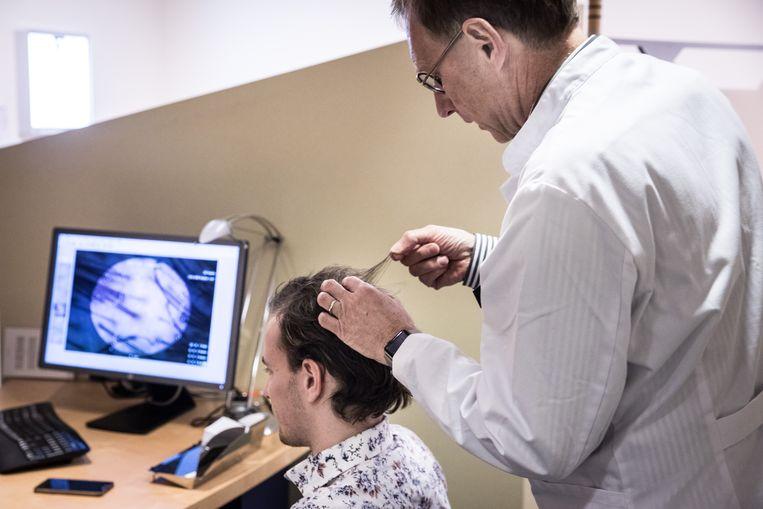 Dokter Rob van Zandvoort bekijkt het haar van de 25-jarige Timo in het Tilburgse Haarkabinet.