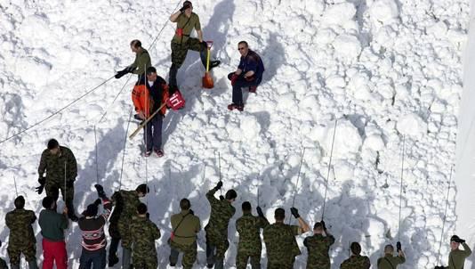 Met man en macht zoekt een groep reddingswerkers naar overlevenden van een lawine in Zwitserland (2012).