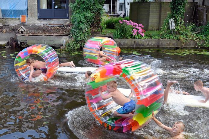 Vol enthousiasme proberen kinderen tijdens het Waterspektakel van speeltuin Kindervreugd zo snel mogelijk over de Giessen te rennen in hun opblaasbare waterradje. Veel gespetter en een kleurrijk beeld.