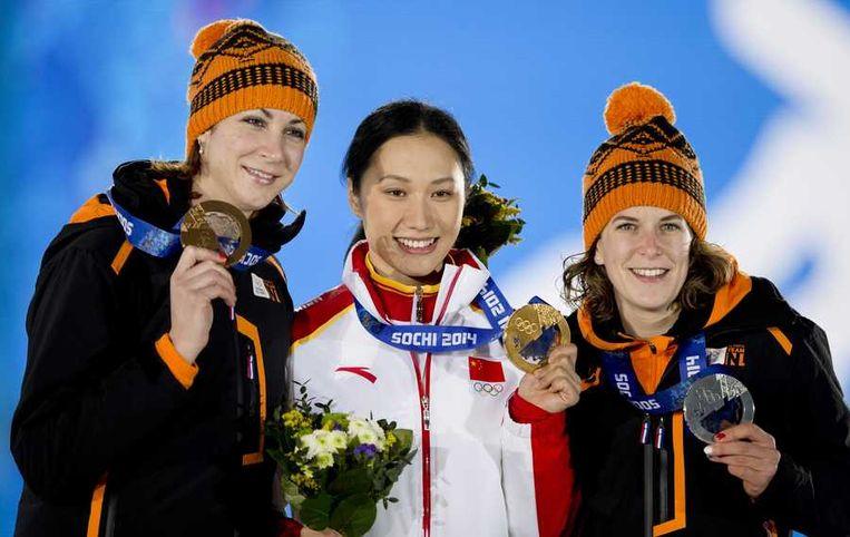 Zilveren medaille-winnaar Ireen Wust (R) en Margot Boer met het brons voor hun rit op de 1000 meter op Medal Plaza. In het midden de Chinese Hong Zhang met het goud. Beeld anp