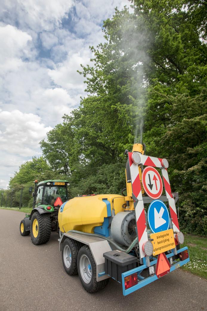 Een bedrijf bespuit in Eindhoven eiken preventief met een biologisch middel.