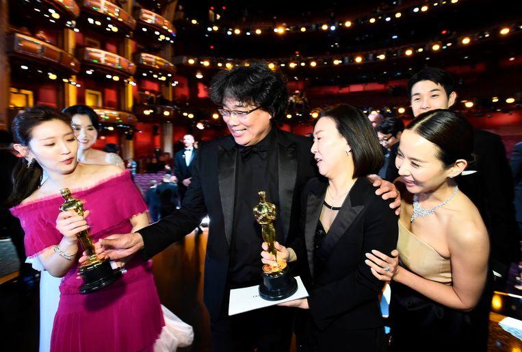 De makers van Parasite poseren op het Oscars-podium. Beeld AFP